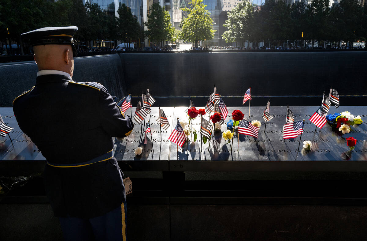 Flags and flowers adorn the names of the victims of the attacks of Sept. 11, 2001, at the Natio ...