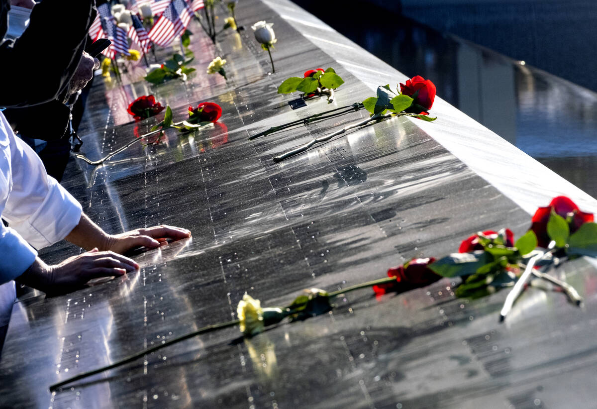 Flowers adorn the names of people who were killed during the attacks on the World Trade Center ...