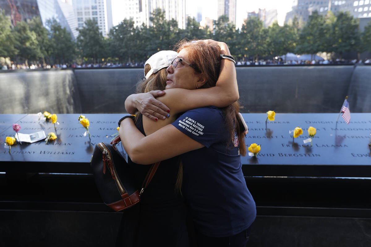 Melinda Moran and Haydee Lillo embrace after finding out they lost people who knew each other, ...