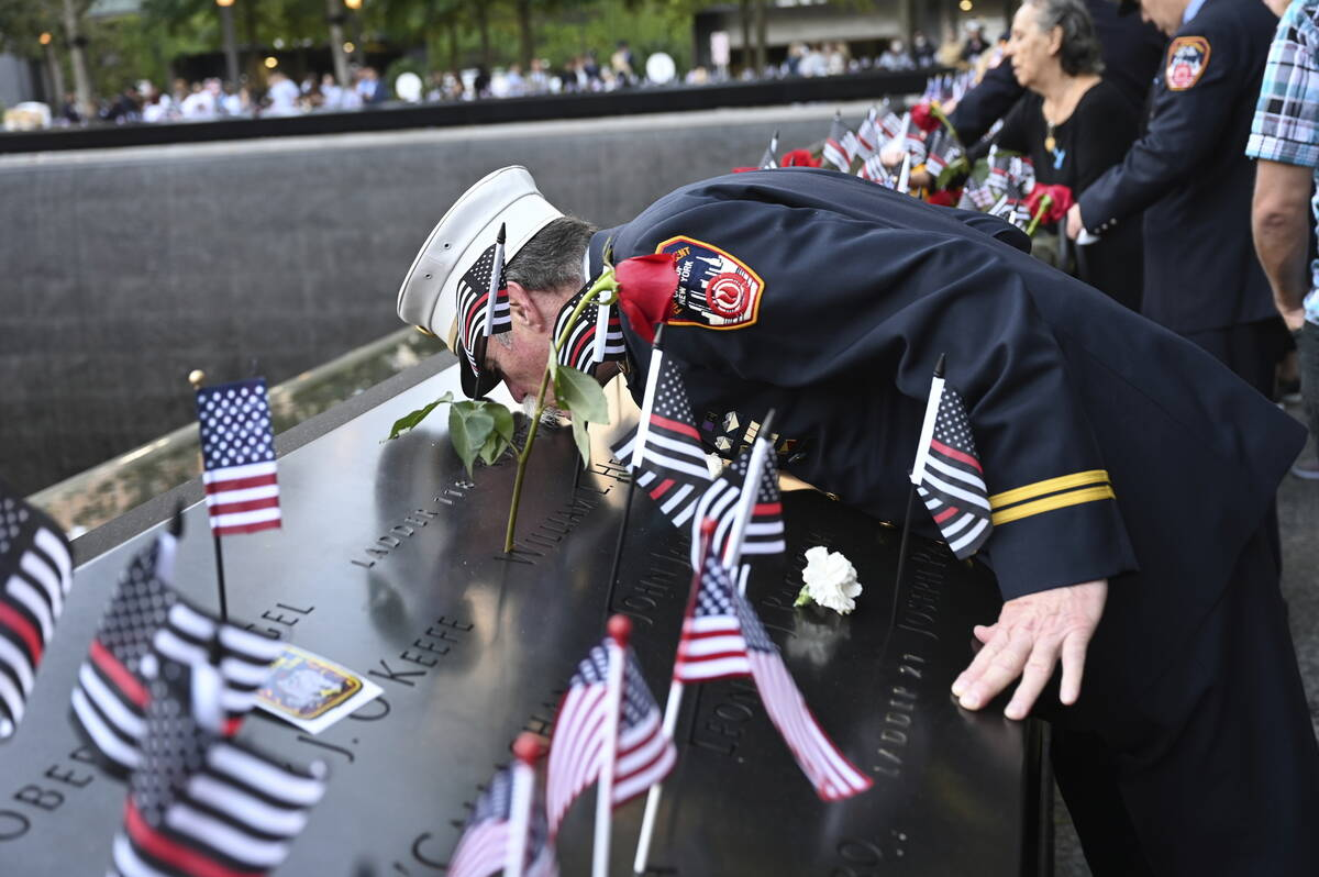 Retired Paramedic Chief Charlie Wells kisses the name of a relative killed in the attack on the ...