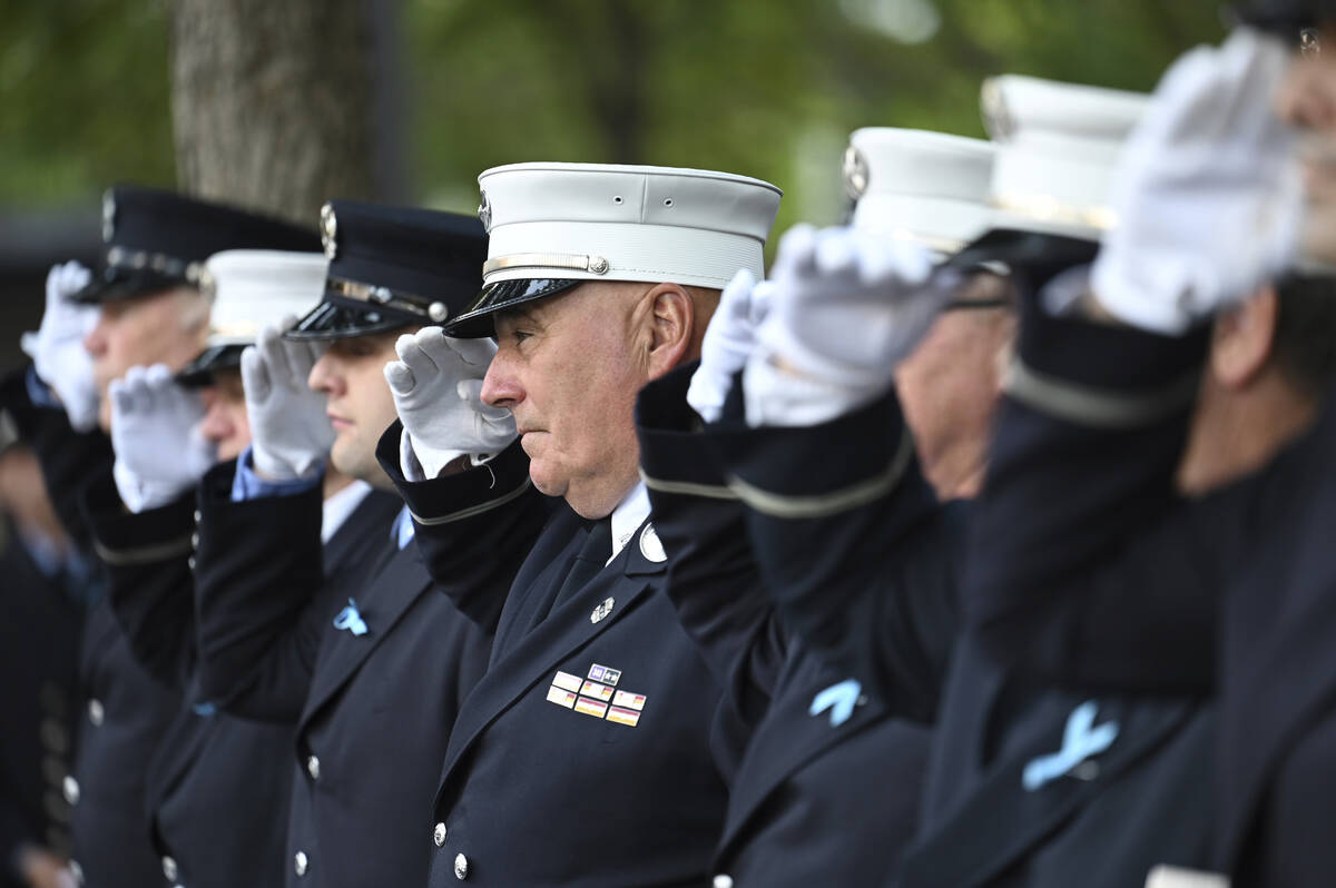 Firefighters salute at the National September 11 Memorial in New York on the 20th anniversary o ...