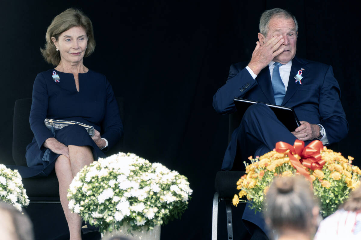 Former President George W. Bush, right, wipes his eyes next to former first lady Laura Bush, af ...