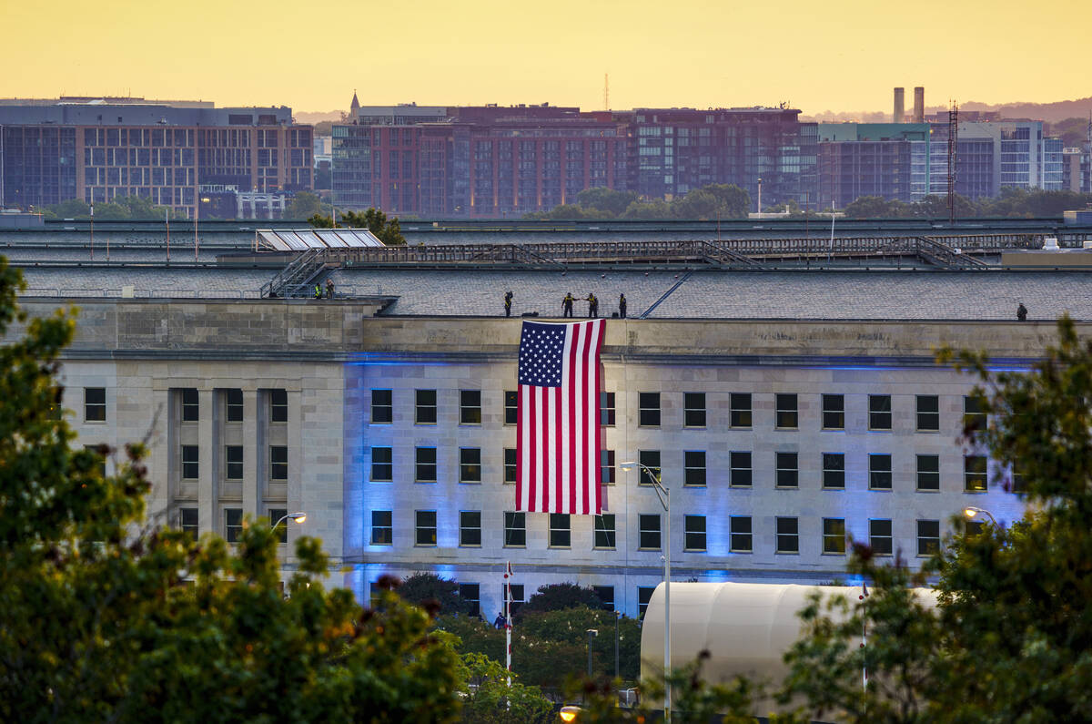 An American flag is unfurled at the Pentagon in Washington, Saturday, Sept. 11, 2021, at sunris ...