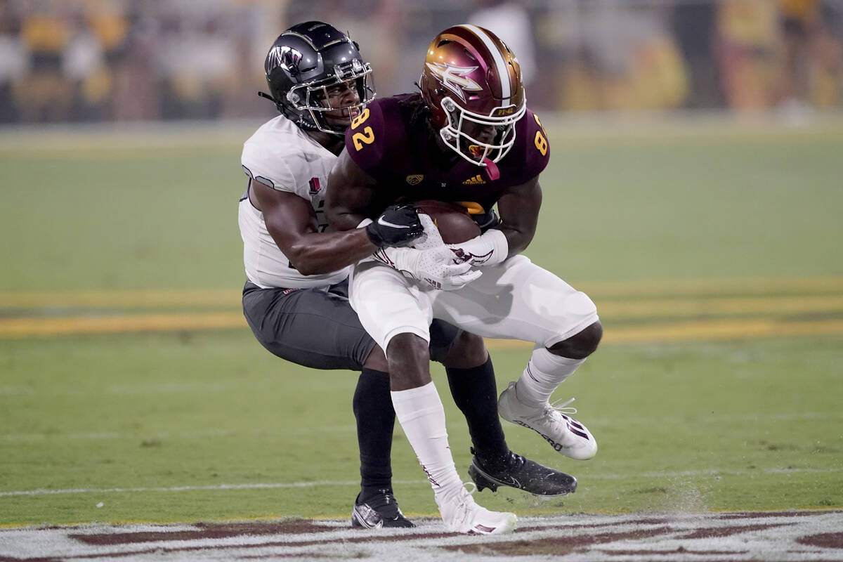UNLV defensive back Aaron Lewis tackles Arizona State wide receiver Andre Johnson (82) during t ...