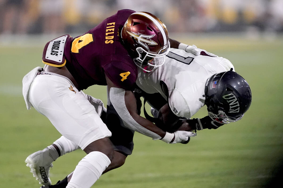 UNLV wide receiver Kyle Williams (1) is tackled by Arizona State defensive back Evan Fields (4) ...