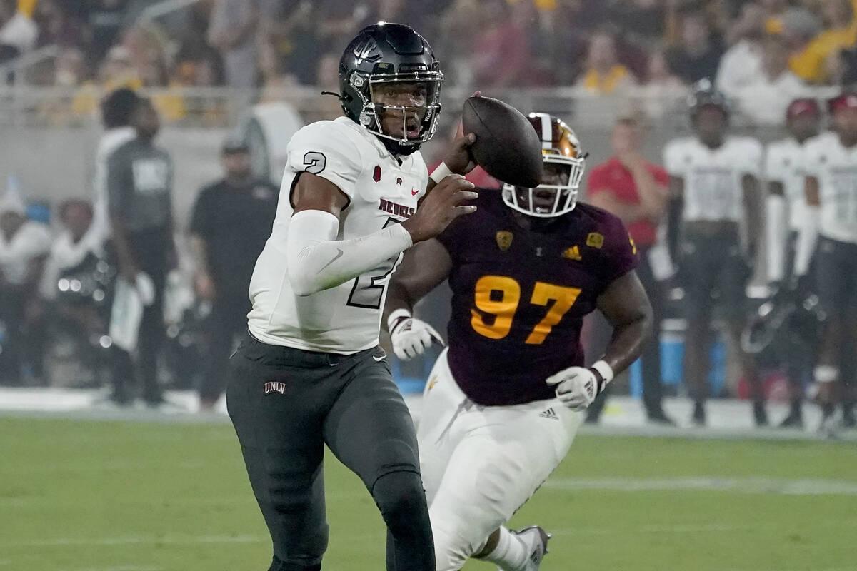UNLV quarterback Doug Brumfield (2) scrambles as Arizona State defensive lineman Shannon Forman ...
