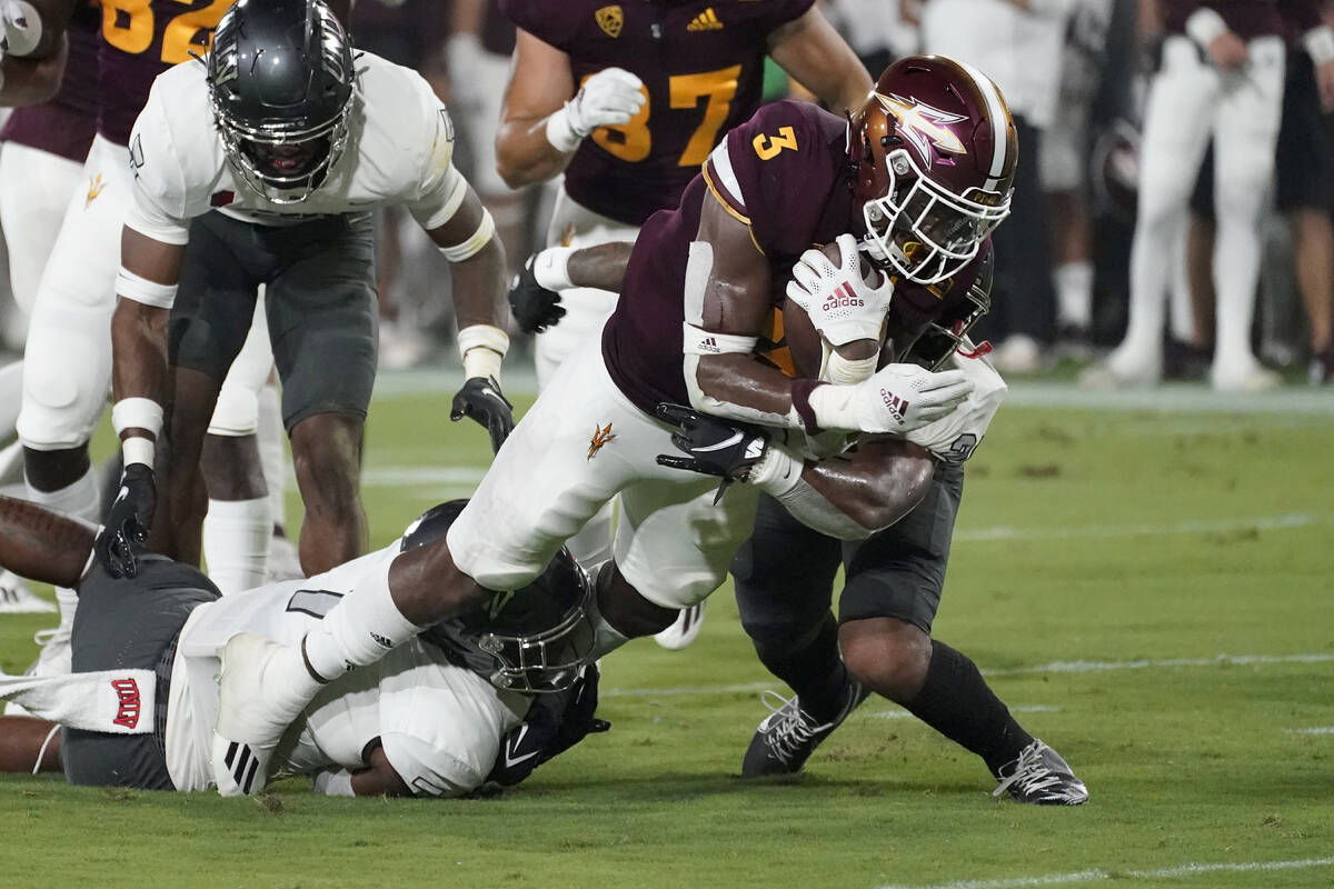 Arizona State running back Rachaad White (3) is hit by UNLV defensive back Bryce Jackson, right ...