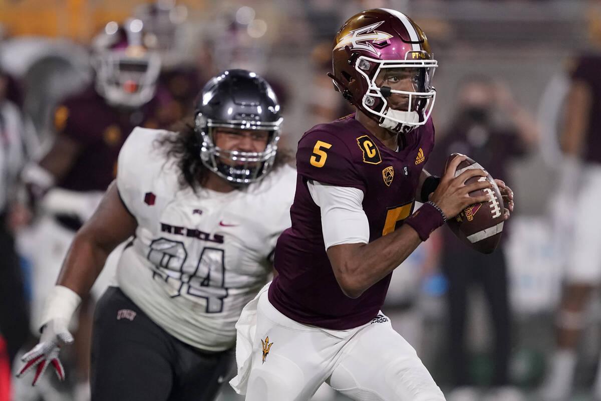 Arizona State quarterback Jayden Daniels (5) looks to throw as UNLV defensive lineman Kolo Uasi ...