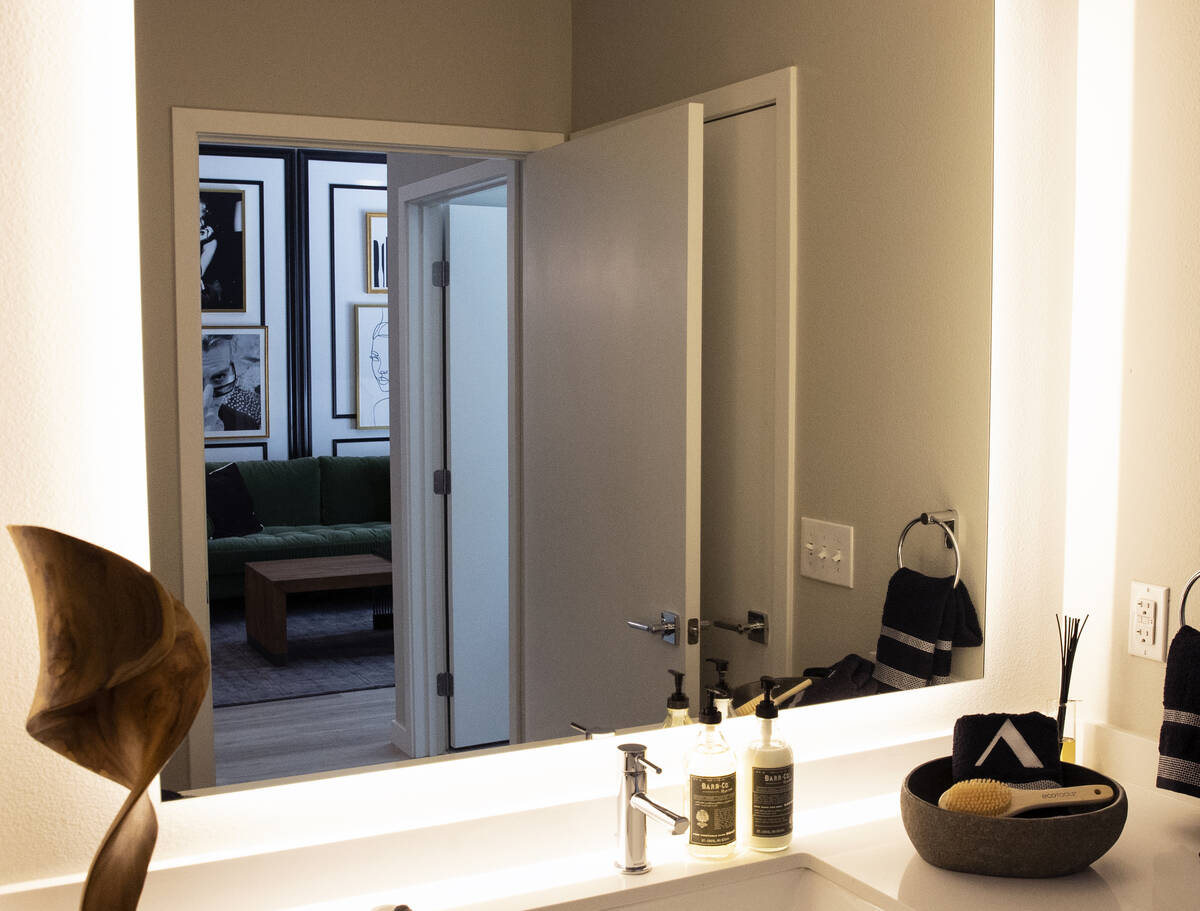 A living room is reflected through a bathroom glass in a one-bedroom apartment at Auric Symphon ...