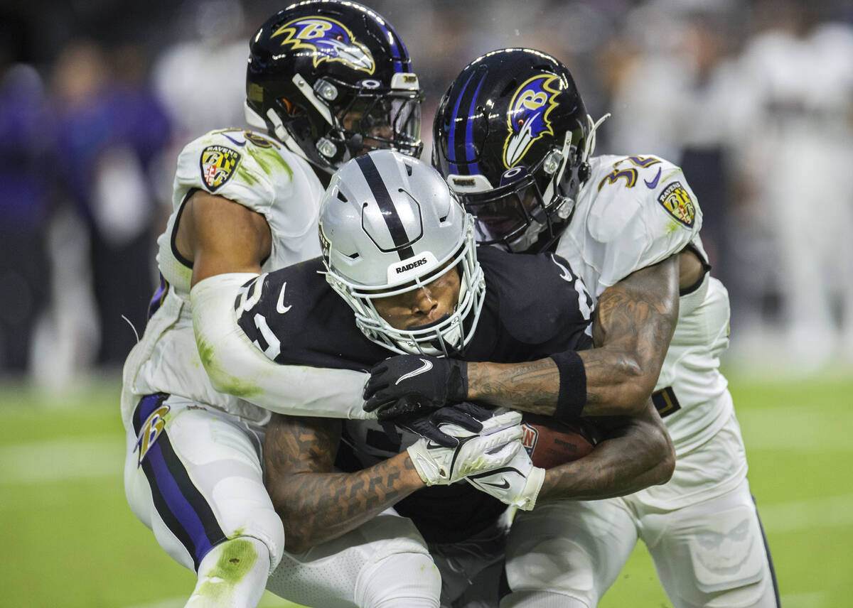 Raiders tight end Darren Waller (83) is tackled by Baltimore defenders in the third quarter dur ...