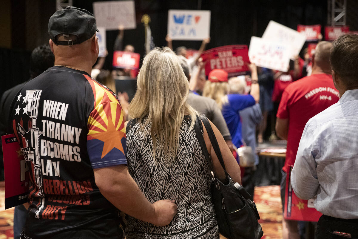 """An attendee wears a shirt saying """"when tyranny becomes law rebellion becomes duty"""" du ..."""