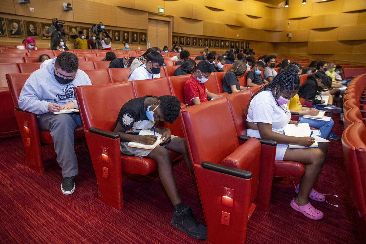 Participants write in a journal during an exercise at a youth mental health conversation as par ...