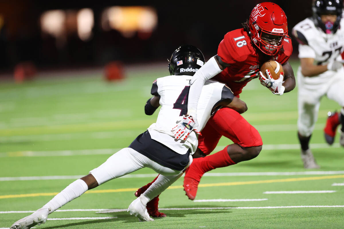 Arbor View's David Washington (18) is tackled by Faith Lutheran's Damien Virgil (4) after a gai ...