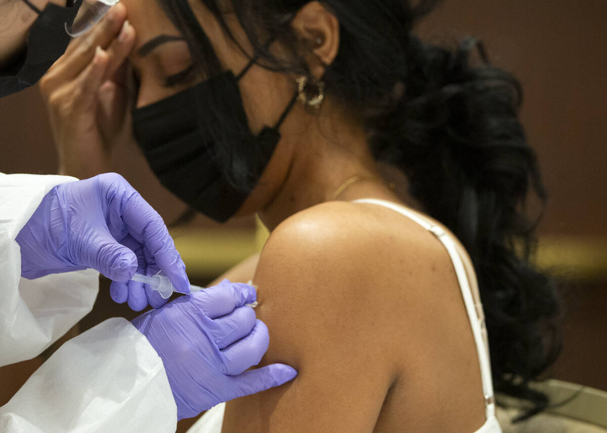 Selam Shumie, a cocktail server at Resorts World Las Vegas, receives her COVID-19 vaccination d ...