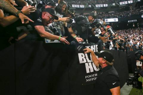 Raiders head coach Jon Gruden celebrates with fans in the black hole after an overtime win agai ...