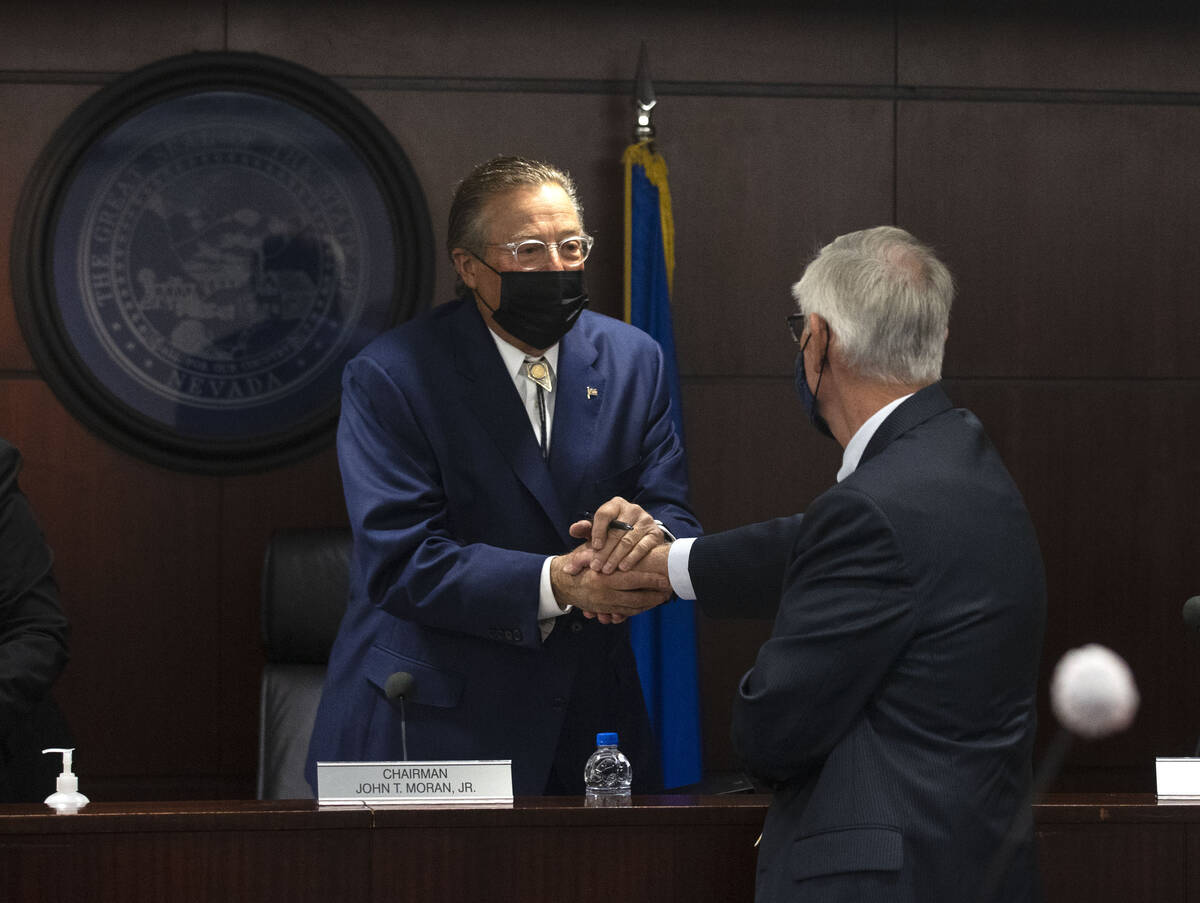 John Moran, left, chairman of the Nevada Gaming Commission, shakes hands with Dan Reaser, a gam ...