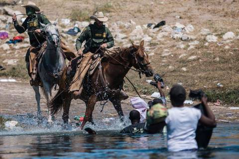 U.S. Customs and Border Protection mounted officers attempt to contain migrants as they cross t ...