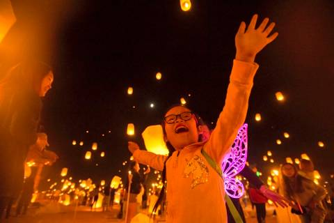 Keira Wang, 5, from Rosemead, Calif., watches lanterns be released during the RiSE festival on ...