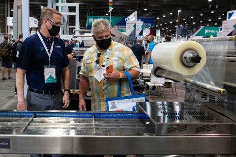 Brian Guillaume, left, of ProMach, talks about ReeEco, an automatic tray sealer, to a potential ...