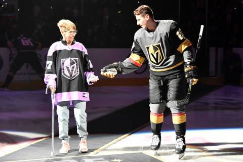 Shea Theodore of the Vegas Golden Knights escorts his grandmother, Kay Darlington, to center ic ...