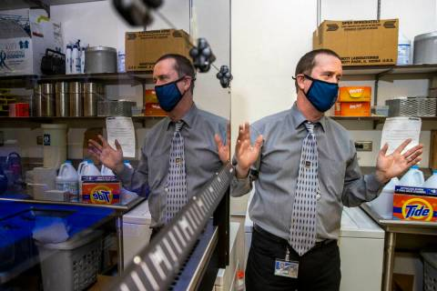 Dr. Mark Pandori, Director of the Nevada State Public Health Lab, with one of their automated g ...