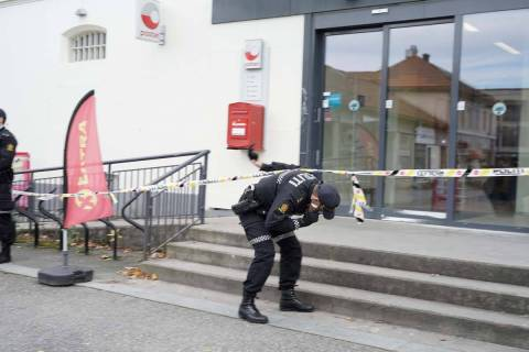 Police search for evidence outside the Coop store in after a man killed several people, in Kong ...