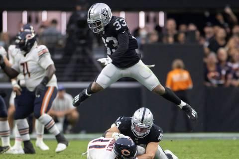 Raiders safety Roderic Teamer (33) leaps over Raiders inside linebacker Nick Kwiatkoski (44) an ...