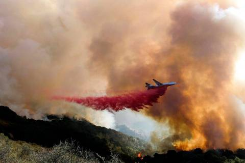 In this Oct. 13, 2021, file photo, an air tanker drops retardant on a wildfire in Goleta, Calif ...
