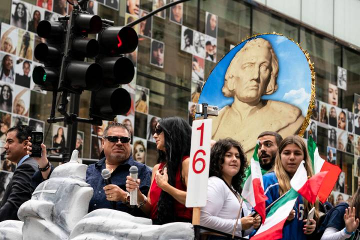 A likeness of Christopher Columbus is displayed atop a float as participants roll up Fifth Aven ...