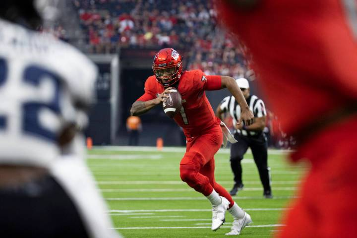 UNLV Rebels quarterback Cameron Friel (7) scrambles past Utah State Aggies cornerback Michael A ...