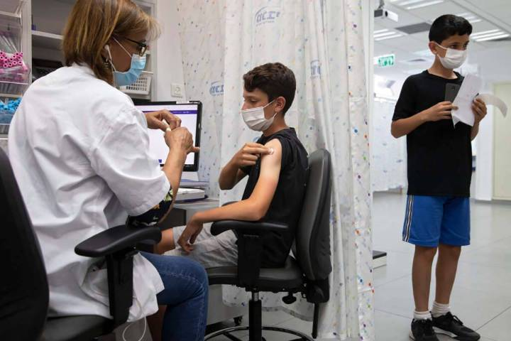 In this June 6, 2021 file photo, a youth receives a Pfizer-BioNTech COVID-19 vaccine in the cen ...