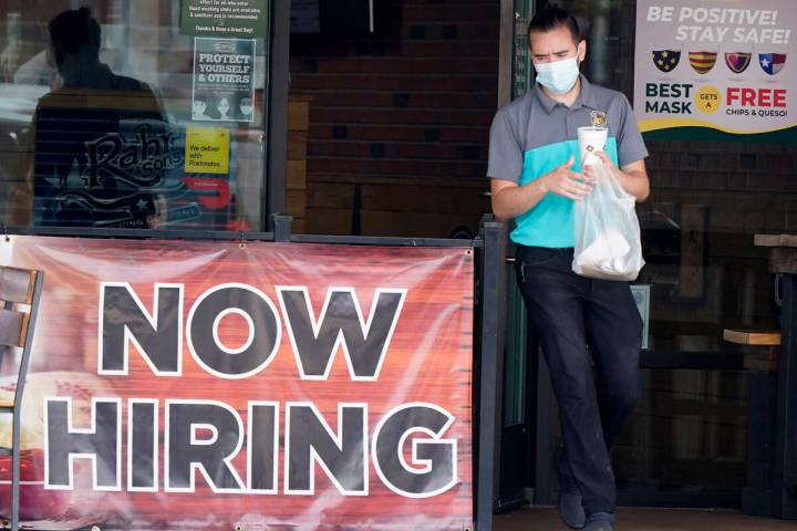 In this Sept. 2, 2020, file photo, a customer wears a face mask as they carry their order past ...