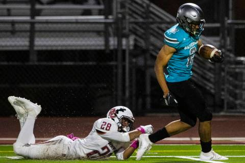 Desert Oasis defensive end Xzavery Simi (28) unable to stop Silverado High's running back Donav ...